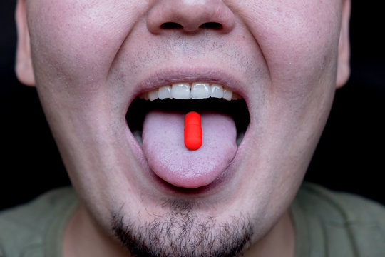 Man's face with red pill on his tongue. Red pill decision for concept design. Pharmacy concept.
