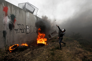 A Palestinian demonstrator hurls stones at Israeli forces as tires burn near the Israeli barrier during a protest against the U.S. President Donald Trump's Middle East peace plan, in the village of Bilin in the Israeli-occupied West Bank