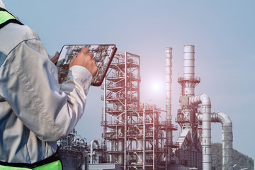 Engenner worker with tablet search information in oil refinery plant.