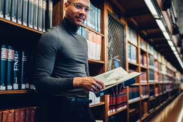 Half length portrait of intellectual professor of history in bifocal eyewear looking at camera while holding literature book in hand for making research of information for new science publication