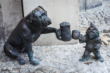 Wroclaw, Poland - December 2, 2019: Dwarf and dog statuette in historic part of Wroclaw city