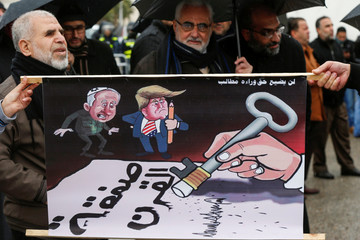 """Protesters hold a caricature image reading in Arabic """"No right will be lost as demands continue"""" during a protest against U.S. President Donald Trump's proposed Middle East peace plan, near the U.S. Embassy in Amman"""