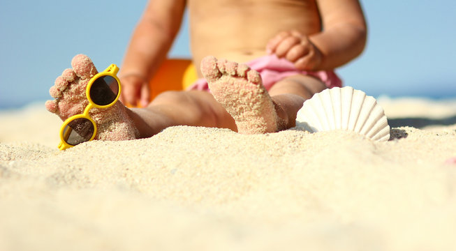 Legs of a child on the sand on the beach