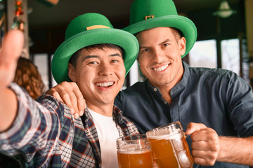Young friends taking selfie during celebrating St. Patrick's Day in pub