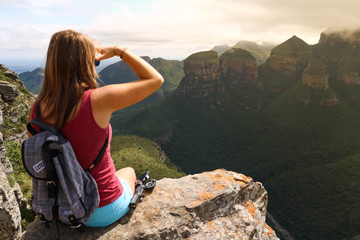 female hiking tourist sitting on mountains and enjoying the view Wall mural