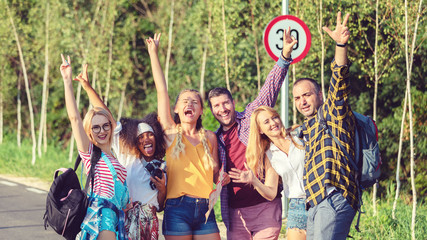 Group of multiracial best friends having fun in nature with raised arms during travel adventure in countryside road
