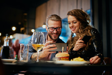 Cute caucasian fashionable couple sitting in restaurant at dinner and taking selfie.