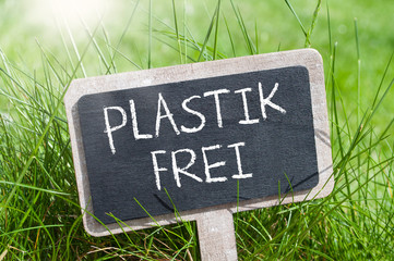Minitature chalkboard in the grass with german words for plastic free - plastik frei