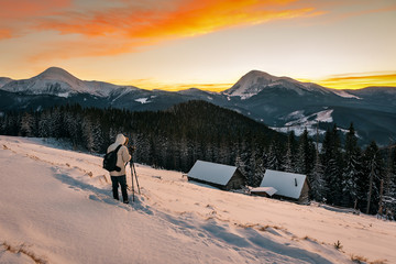 photographer taking pictures of sunset in winter mountains