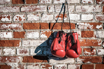 red boxing gloves on old brick wall
