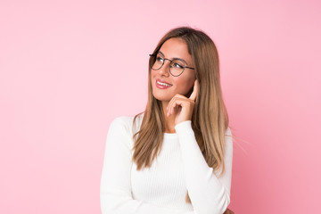 Young blonde woman over isolated pink background with glasses Wall mural