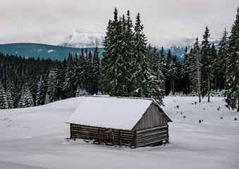 wooden snow covered cabin in winter mountains