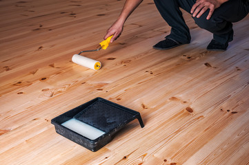 worker lacquers the wooden floor