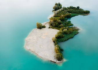 Aerial view of magical forest island in a turquoise lake