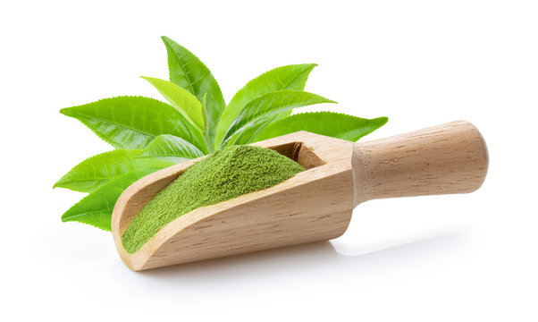 matcha green tea powder in wood scoop and leaf on white