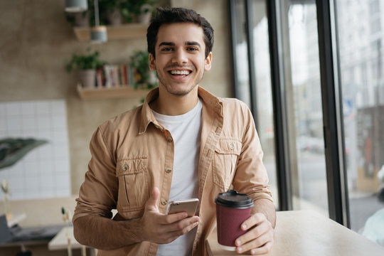 Happy Indian man holding cup of coffee and smartphone looking at camera, standing in cafe. Positive asian hipster using mobile app for online shopping, booking tickets on website and smiling