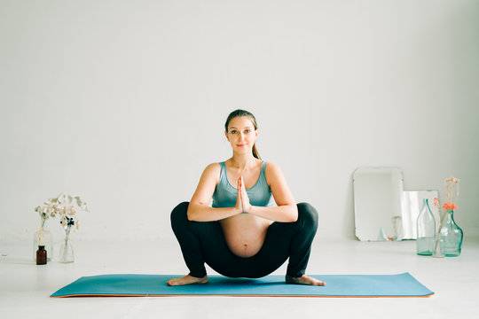 a young pretty pregnant girl in sports clothes is doing yoga, doing asana Malasana on the Mat in the Studio