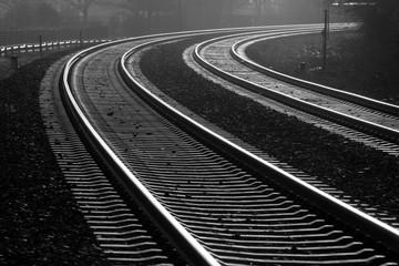 Fotorollo Eisenbahnschienen Schienen Gleise Kurve zweigleisig Eisenbahn Strecke Schotter Profil Stahl Rost Schrauben Verkehr Transport Zukunft Nebenstrecke Hauptstrecke Deutschland Schwarz weiß