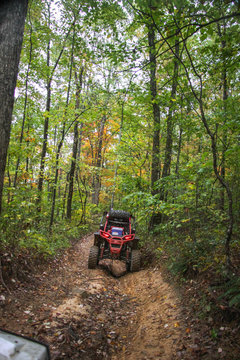 Buggie stradling trench on trail in woods of TN