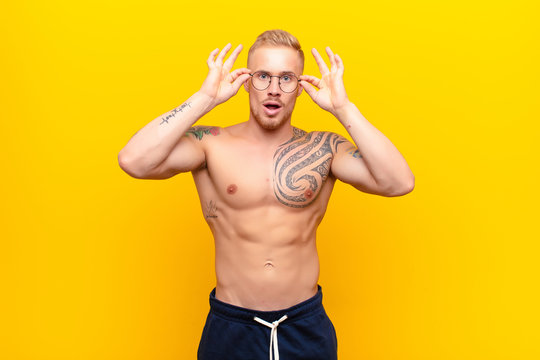 young strong blonde man feeling shocked, amazed and surprised, holding glasses with astonished, disbelieving look against yellow wall