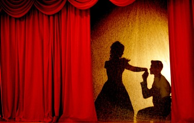 A man and woman in theatrical costumes in the theater of shadows on the stage with red curtains. Love in the shadows theatre. Red curtain of opera, cinema or theater stage drapes.