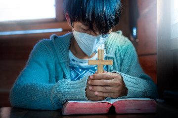 Close up hands of christian in mask praying with holding Cross on Bible, Christian treatment concept.