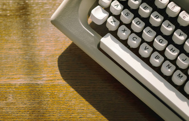 Close up old typewriter on wooden desk with sunlight