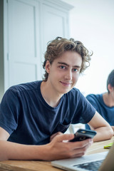 Portrait of smiling teenage boy with smartphone and laptop at home