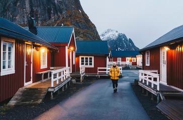 Tourist exploring the fishing village Hamnoy, Lofoten, Norway