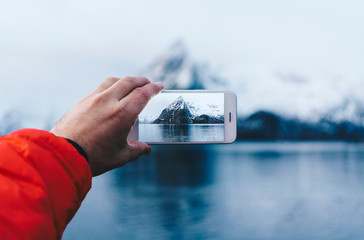 Close-up of tourist taking a smartphone picture at Hamnoy, Lofoten, Norway