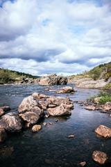 Landscape image of wide river with big rocks, Lakselv, Norway