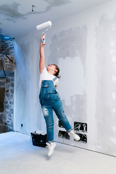 Girl jumping while painting a wall in a house