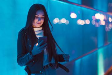 Portrait of smiling teenage girl leaning against blue glass pane looking at smartphone Fotobehang