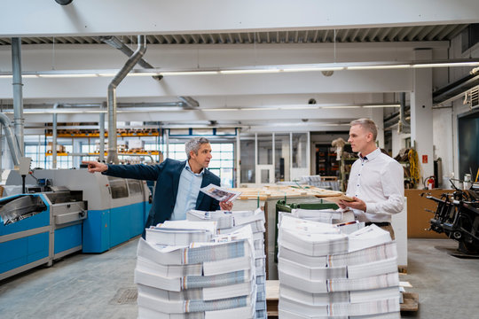 Two businessmen at stack of papers in a factory