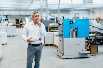 Man in white shirt in a factory looking around