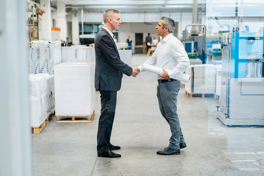 Two businessmen shaking hands in a factory