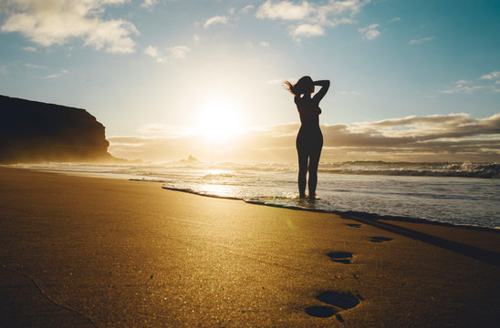 Woman standing on the beach at sunset