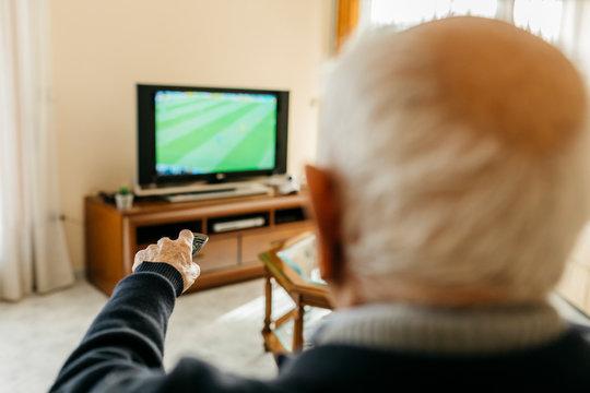 Back view of senior man watching TV at home