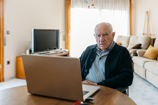 Portrait of content senior man in wheelchair with laptop at home