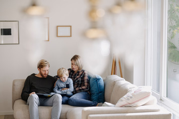Family looking at book on couch at home