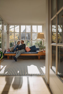 Affectionate couple relaxing in sunroom at home
