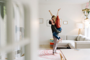 Man lifting and embracing his cheering wife