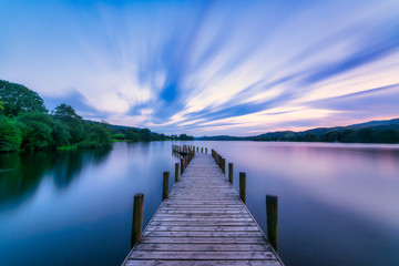 UK, England, Long exposure of clouds over jetty on Coniston Water lake at dusk