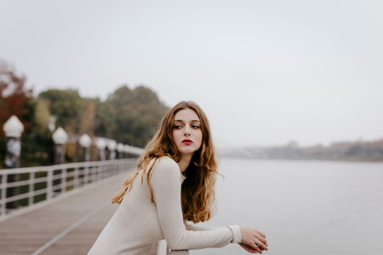 Portrait of young woman wearing white dress, leaning on railing on rainy day