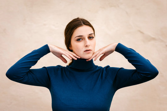 Close up portrait of woman with blue turtleneck pullover, hands on chin