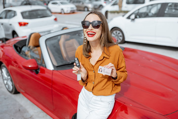 Portrait of a beautiful young woman standing with driver's license and keys near the red cabriolet at the car parking. Concept of a happy buying or renting a car
