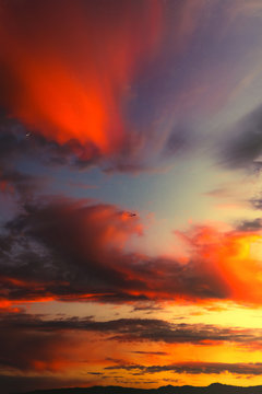 Colorful Sunset Sky with Dramatic Clouds over the Mountains as an airplane flies above in Northern California