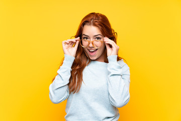 Teenager redhead girl over isolated yellow background with glasses and surprised Fototapete