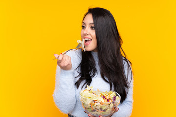 Young Colombian girl holding a salad over isolated background