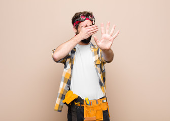young housekeeper man covering face with hand and putting other hand up front to stop camera, refusing photos or pictures against flat wall